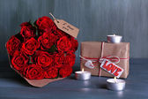 Bouquet of red roses wrapped in paper with present box and candles on wooden background — Stock Photo