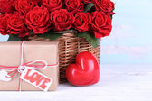 Bouquet of red roses in basket with present box on wooden background — Stock Photo