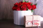 Bouquet of red roses in textile box with present on wooden background — Stock Photo