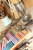 Paintbrushes with colorful chalk pastels in box on fabric background — Stock Photo