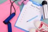 Meal plan and sports equipment top view close-up — Stock Photo