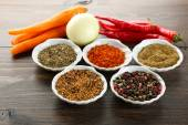 Different kinds of spices in bowls close-up, on wooden background — Stock Photo