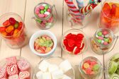 Sweetness in different containers on wooden background — Stock Photo