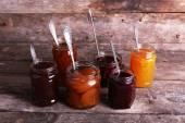 Jars of tasty jam on wooden background — Stock Photo