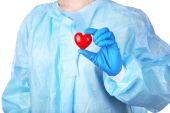 Doctor holding decorative heart on blue background — Stock fotografie