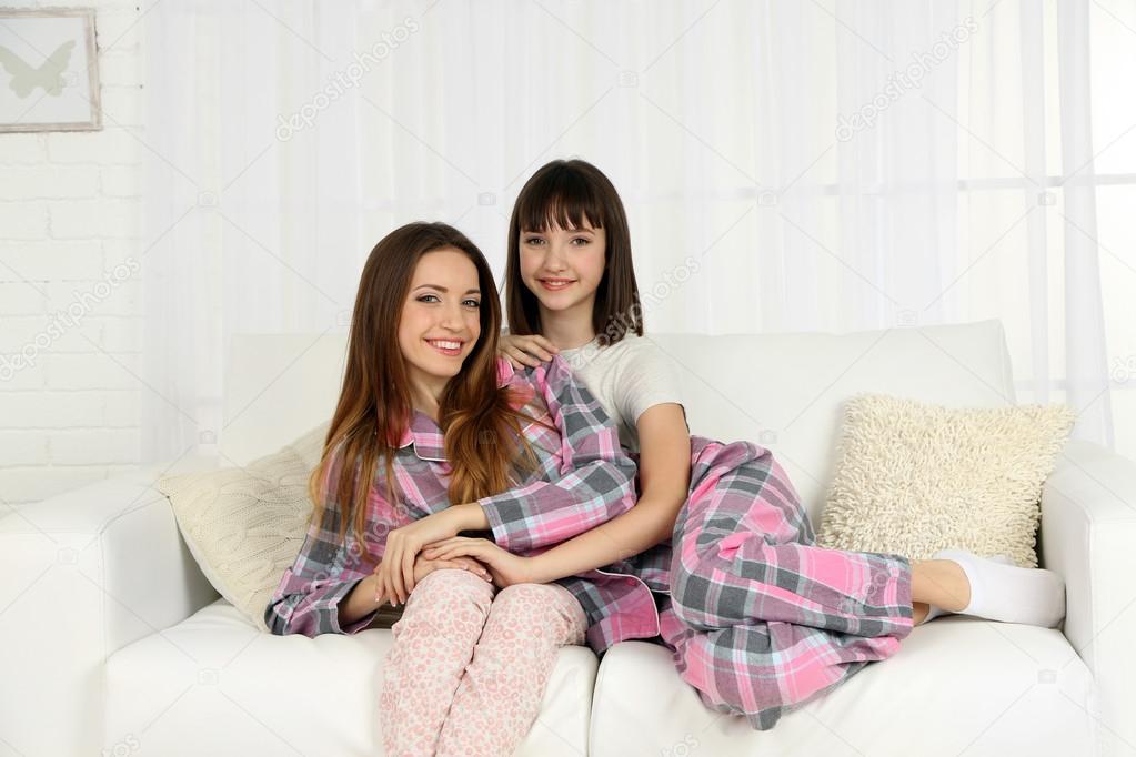Two girls in pajamas sitting on sofa — Stock Photo © belchonock ...