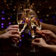 Clinking glasses of champagne in hands on bright lights background — Stock Photo #66902161
