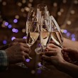 Clinking glasses of champagne in hands on bright lights background — Stock Photo #66902177