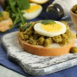 Sandwiches with green peas paste and boiled egg on cutting board with napkin on color wooden planks background — Stock Photo #66902337