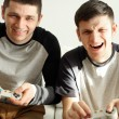 Two handsome young men playing video games in room — Stock Photo #66906071