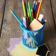Colorful pencils in metal holder with sticky notes on wooden planks background — Stock Photo #66906887