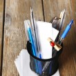 Different pens in metal holder with paper notes on wooden planks background — Stock Photo #66906905