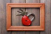 Heart-shaped padlock with key on wooden background — Stock Photo