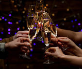 Clinking glasses of champagne in hands on bright lights background — Stock Photo