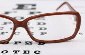 Eye glasses on eyesight test chart background — Stock Photo