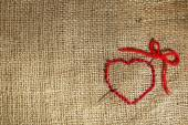 Linen canvas with red heart embroidered on it, close-up — Stock Photo