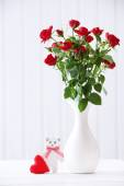 Bouquet of red roses in vase on wooden planks background — Stock Photo