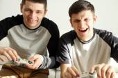 Two handsome young men playing video games in room — Zdjęcie stockowe