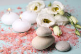 Spa stones with candles and flowers on blue background close-up — Stock Photo