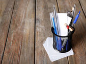 Different pens in metal holder with paper notes on wooden planks background — Stock Photo
