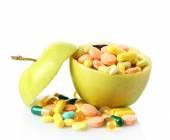 Apple and colorful pills, isolated on white — Stock fotografie