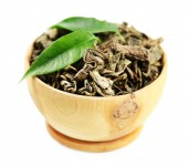 Wooden bowl with green tea with leaf isolated on white  — Stock Photo