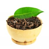 Wooden bowl with black tea with leaf isolated on white  — Stock Photo