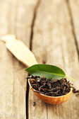 Black tea with leaf in spoon on old wooden table — Stock Photo