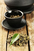 Green tea with leaf on old wooden table — Stock Photo