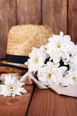 Hat with flowers on wooden background — Stock Photo