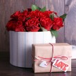 Bouquet of red roses in textile box with present on wooden background — Stock Photo #67006847