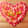 Words I Love You formed from cubes on  petals of roses on wooden background — Foto de Stock   #67007739