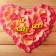 Words I Love You formed from cubes on  petals of roses on wooden background — Stock fotografie #67007739
