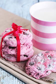 Pink cookies and cup with milk on table close-up — Stock Photo