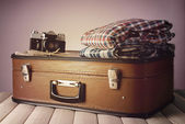 Vintage suitcase with clothes and camera on table on dark colorful background — Stock Photo