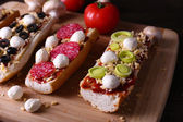 Different sandwiches with vegetables and cheese on cutting board on table close up — Fotografia Stock