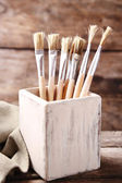 Paint brushes on old wooden background — Stock Photo