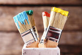 Brushes with colorful paints on old wooden background — Stock Photo