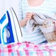 Electric iron and shirt on ironing board in room — Stock Photo #67012043