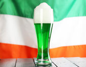 Glass of green beer on flag background — Stock Photo