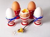 Boiled eggs in holders on light   background — Stock Photo