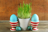 Fresh green grass in small metal bucket and Easter eggs in holders, on wooden background — Stock Photo
