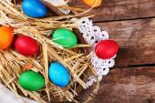 Easter eggs on tray with straw on vintage wooden planks background — Stock Photo