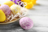 Easter composition with colorful eggs on plate on wooden table background — 图库照片
