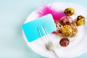 Easter table setting with empty card and Easter eggs on color wooden background — Stock Photo