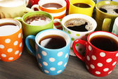 Many cups of coffee on wooden table, closeup — Stock Photo