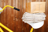 Vintage yellow bicycle with newspaper and parcel, on wooden wall background — Foto de Stock