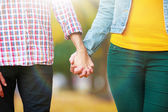 Loving couple holding hands outdoors on sunny nature background — Stock Photo