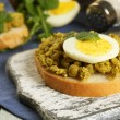 Sandwiches with green peas paste and boiled egg on cutting board with napkin on color wooden planks background — Stock Photo #67202793
