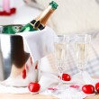 Champagne bottle in bucket,  glasses and rose petals for celebrating Valentines Day — Stock Photo #67203137